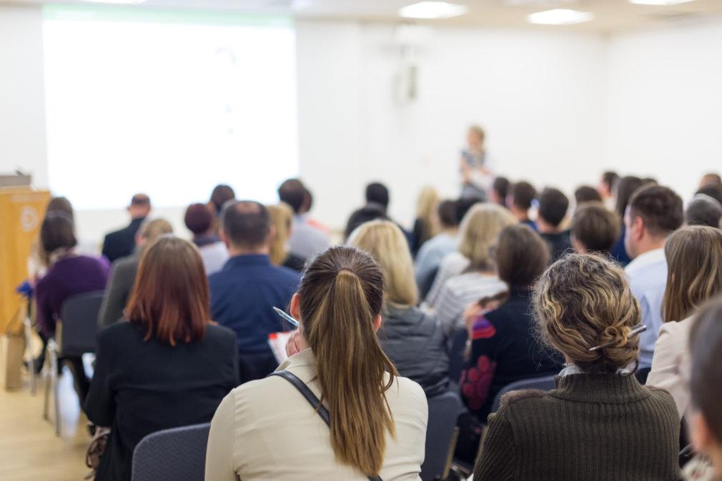 Luokkahuoneessa yleisö kuuntelee luennoitsijaa.