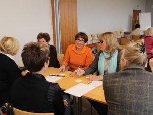 Naisia pöydän ääressä kokoushuoneessa keskustelemassa.