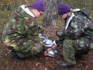 Naiset opettelevat trangian käyttöä metsässä.