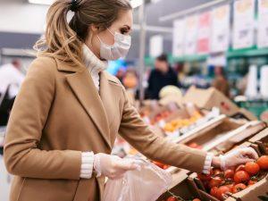 Asiakas kaupassa maski kasvoillaan valitsemassa hedelmiä.