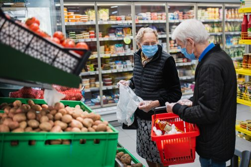 Iäkäs pariskunta kaupassa maskit kasvoillaan.