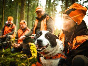 Metsästäjiä ja metsästyskoira metsässä.